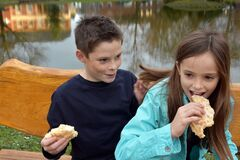Free Siblings Sharing A Piece Of Pastry Royalty Free Stock Photos - 186778998
