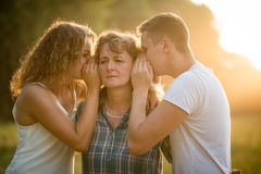 Siblings sharing each other`s secret with mother. Daughter and son whispering secret into mother`s ear Stock Image