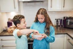 Siblings Sharing Fruit at Home stock photos
