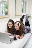 Siblings sharing laptop on sofa Royalty Free Stock Photo
