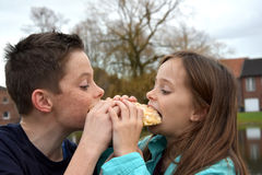 Siblings sharing pastry Stock Image