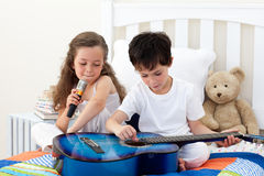 Siblings singing and playing guitar Royalty Free Stock Photography