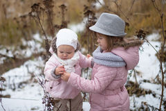 Siblings sister girl in pink jacket and knit scarf and fedora ha stock image