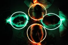 Glow Stick Necklaces in the Dark. Siblings, sisters and brother, in a dark room with green and orange glow stick necklaces over their faces, smiling and having Royalty Free Stock Photos