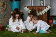 Siblings sisters in nightgowns playing with rabbit. Easter concept Royalty Free Stock Photo