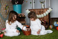 Siblings sisters in nightgowns playing with rabbit. Easter concept Royalty Free Stock Photography
