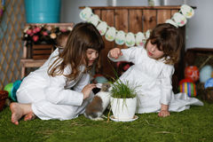 Siblings sisters in nightgowns playing with rabbit. Easter concept Stock Image