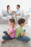 Siblings sitting back to back while parents are arguing Stock Photo