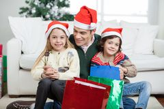 Siblings Sitting On Father's Lap With Christmas Royalty Free Stock Photography