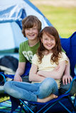 Siblings Sitting Together On Chair With Tent In Background Stock Photos