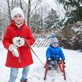 Siblings sledding in winter through Royalty Free Stock Image