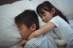 Siblings sleeping on bed in the bed room Stock Image
