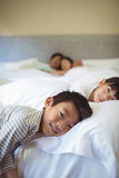 Siblings sleeping on bed in bedroom Stock Photography