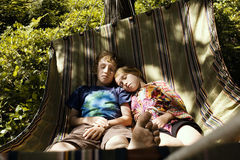 Siblings sleeping on a hammock over lush undergrowth Royalty Free Stock Images