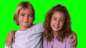 Siblings smiling on green screen Stock Image
