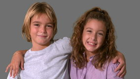 Siblings smiling on grey background Royalty Free Stock Photo
