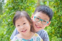 Siblings smiling in park Royalty Free Stock Photos