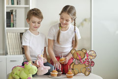 Siblings and soft toys celebrating birthday with cup cakes Royalty Free Stock Image