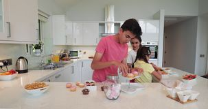 Siblings Sorting in the Kitchen. Front view of teenage boy sorting cupcakes onto a cupcake stand. Two little girls preparing and sorting through party food in stock footage