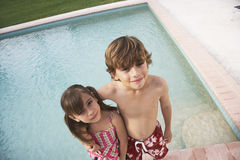 Siblings Standing At The Edge Of Swimming Pool Royalty Free Stock Photography
