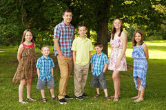 Siblings standing in a family pose Royalty Free Stock Photo