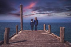 Siblings standing on a wooden pier royalty free stock image