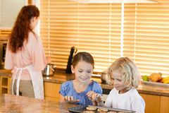 Siblings stealing cookies together Royalty Free Stock Images