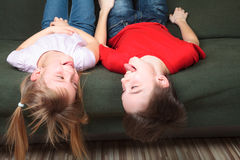 Siblings sticking out tongues on a couch Royalty Free Stock Photos