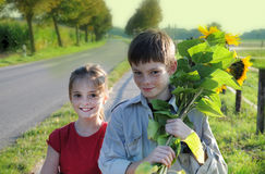 Siblings with sunflowers Royalty Free Stock Images