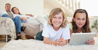 Siblings with tablet on the carpet Royalty Free Stock Image
