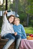 Siblings Taking Selfportrait At Campsite Stock Photos