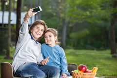 Siblings Taking Selfportrait Through Smartphone At Royalty Free Stock Photos