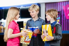 Siblings Talking While Holding Snacks At Cinema Stock Photo