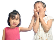 Siblings teasing, asian little girl pulling her sister's ear Stock Images