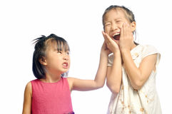 Siblings teasing, asian little girl pulling her sister's ear Stock Image