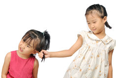 Siblings Teasing, Asian Little Girl Pulling Her Sister S Hair Royalty Free Stock Image