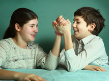 Siblings teenager brother and sister compete arm wrestling royalty free stock photos