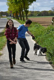 Siblings and their dog. Siblings walking with their little harlequin poodle Royalty Free Stock Image