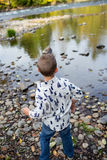 Siblings Throwing Rocks In River Together Stock Photo