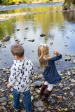 Siblings Throwing Rocks In River Together Stock Image