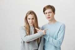 Siblings trying to accuse each other in front of angry mom. Serious unhappy couple with fair hair, frowning and pointing royalty free stock photography