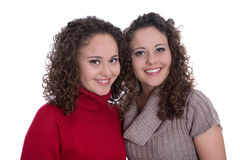 Siblings: two monozygotic young twin womans in portrait isolated. Over white background wearing winter pullovers Stock Photography