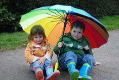 Siblings with umbrella. Siblings outside with a colorful big umbrella Royalty Free Stock Photo