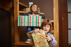 Siblings unwrapping Christmas presents Stock Image