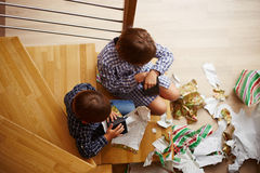 Siblings unwrapping Christmas presents. Two siblings unwrapping Christmas presents Royalty Free Stock Images