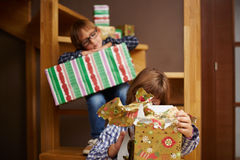Siblings unwrapping Christmas presents. Two siblings unwrapping Christmas presents Stock Image