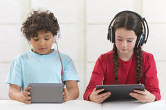 Siblings using digital tablet while listening royalty free stock photo