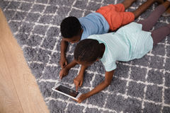 Siblings using digital tablet while lying on rug at home Stock Image