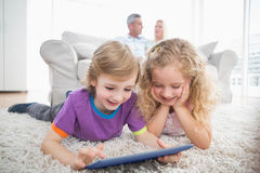 Siblings using digital tablet on rug at home Stock Image