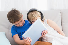 Siblings using a headphone and a tablet sitting on a couch Stock Photos